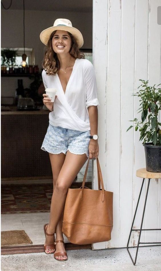 a white wrap shirt, blue lace shorts with a scallop edge, tan sandals, a tan bag and a hat