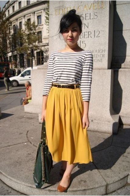 a yellow midi A-line skirt, a striped long sleeve, brown flats and a green bag