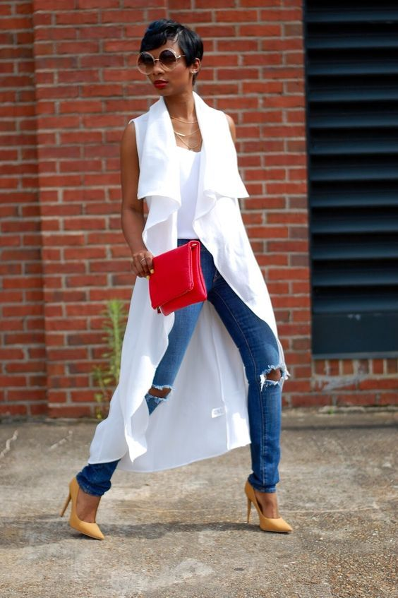 blue ripped skinnies, a white top, a white duster vest, yellow shoes and a red clutch