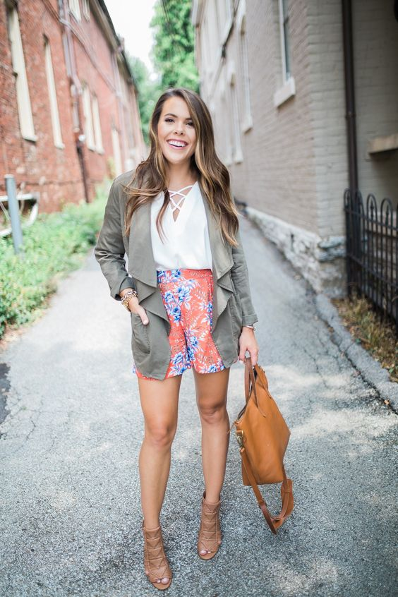 bright floral shorts, a white shirt, brown booties and an olive green coverup