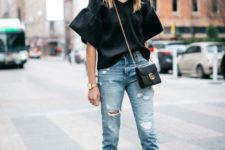 15 ripped blue cropped skinnies, a black oversized shirt with bell sleeves, black heels and a bag