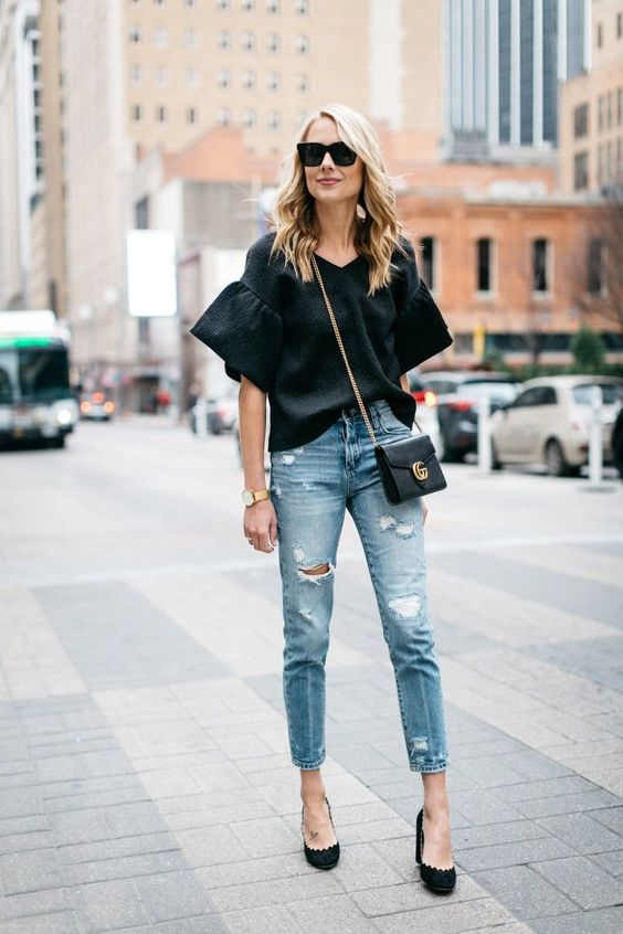 ripped blue cropped skinnies, a black oversized shirt with bell sleeves, black heels and a bag