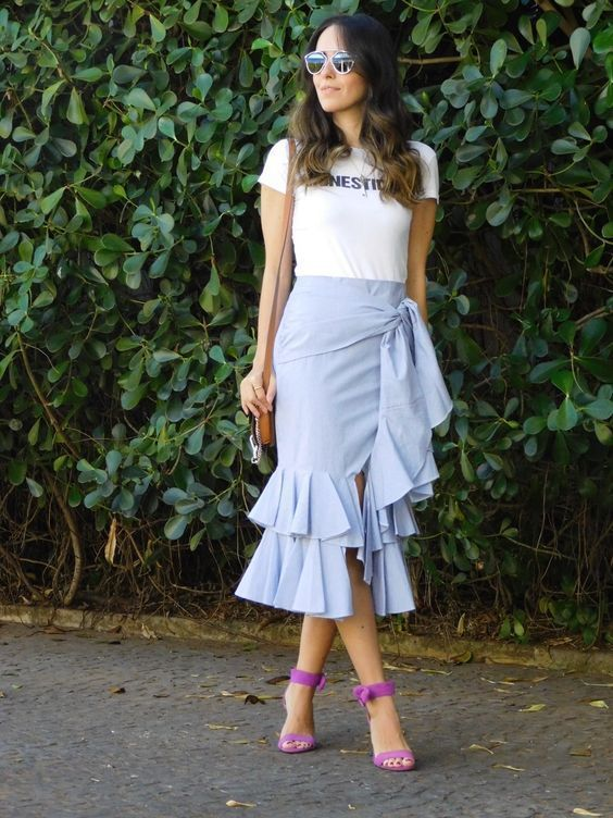 a white t shirt, a powder blue ruffled asymmetrical midi skirt, hot pink shoes and a small bag