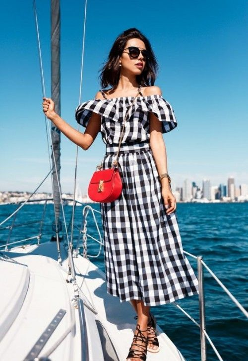 an off the shoulder buffalo plaid black and white midi dress, black lace up sandals and a red bag