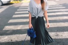 16 an oversized gree tee, a black pleated midi, yellow sneakers and a cobalt blue bag