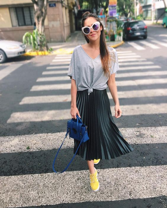 an oversized gree tee, a black pleated midi, yellow sneakers and a cobalt blue bag