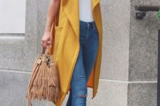 16 blue ripped skinnies, a white top, tan lace up heels, a fringed bag and a yellow duster vest