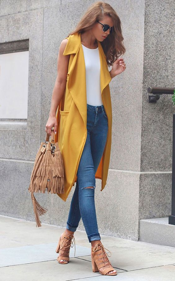 blue ripped skinnies, a white top, tan lace up heels, a fringed bag and a yellow duster vest