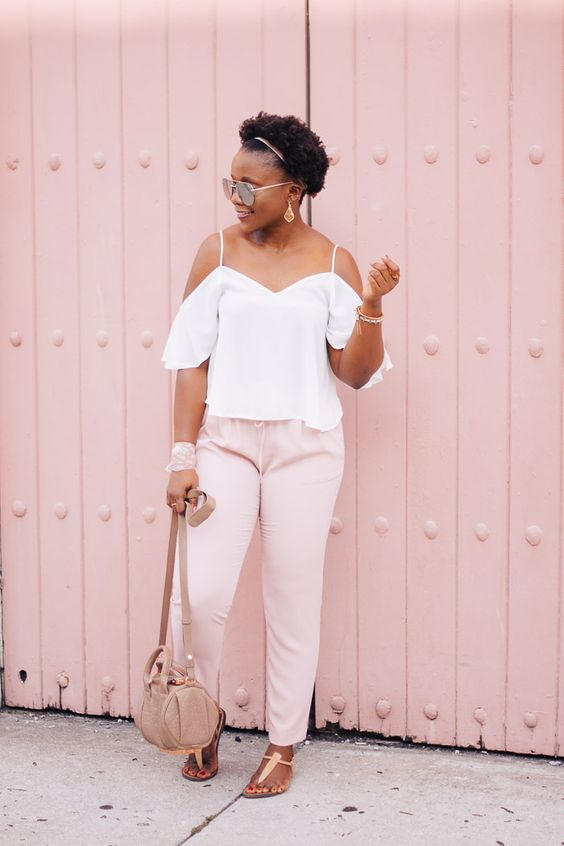 pink pants, a white cold shoulder top, a neutral bag and blush sandals