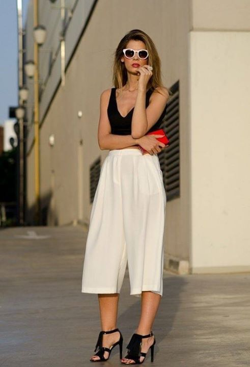white culottes, a black thick strap top, a small red clutch, black fringe shoes