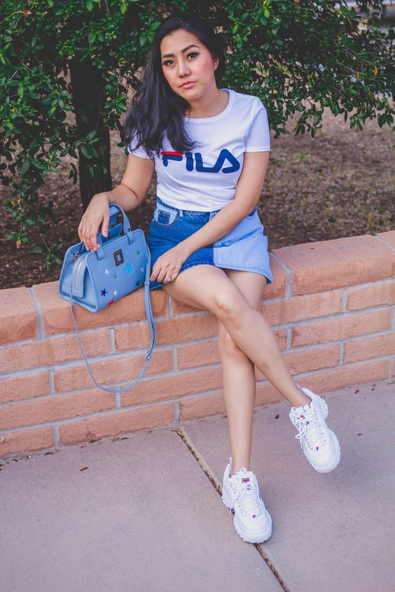 white sneakers, a white logo tee, a denim mini skirt and a blue bag
