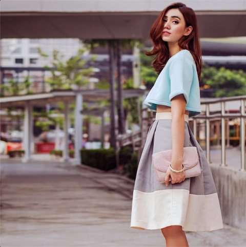 With A-line skirt and pale pink clutch