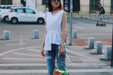 With assymetrical top, jeans and green bag