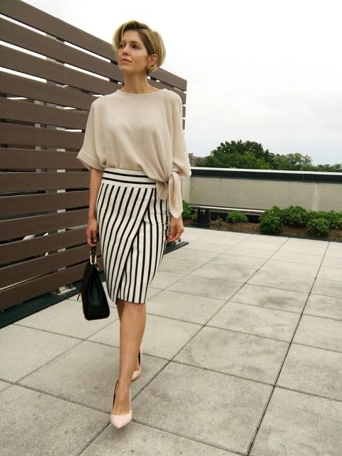 With beige loose blouse, beige pumps and black bag