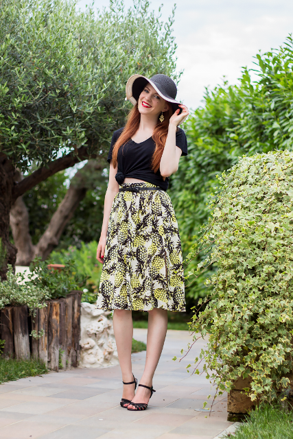 With black crop top, wide brim hat and black heels