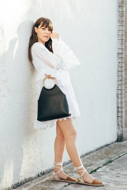 With black leather bag and white and brown flat shoes