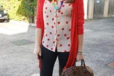 With black skinny pants, red cardigan, printed bag and sneakers