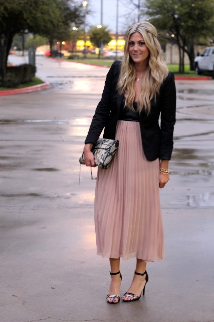 With black top, black blazer, printed clutch and sandals