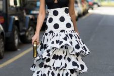 With black top, golden clutch and polka dot shoes