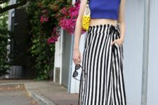 With blue crop top, striped shoes and yellow clutch