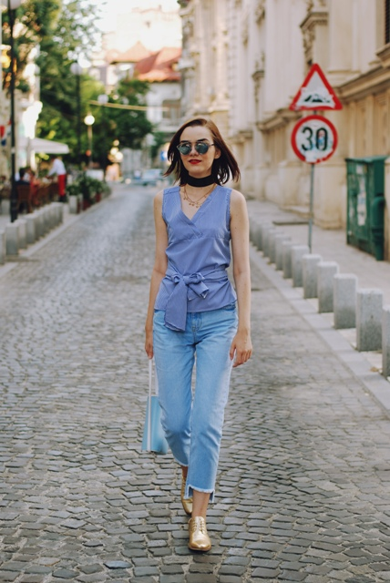 With crop jeans, blue bag and golden flat shoes