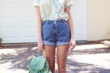 With floral shirt, hat, mint green backpack and flats