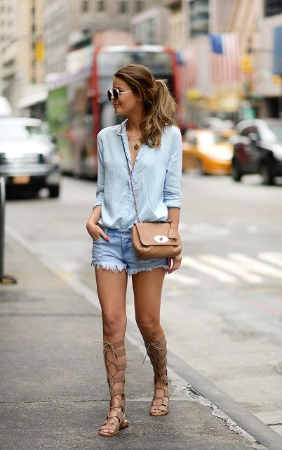 With light blue shirt, beige bag and denim shorts
