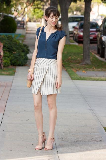 With navy blue shirt, beige heels and beige bag