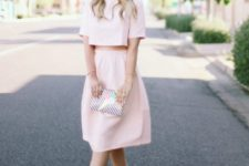 With pale pink skirt, lace up shoes and printed clutch
