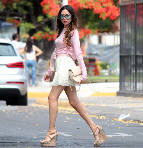With pink shirt, white mini skirt and beige bag