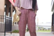 With printed trousers, platform sandals and golden bag