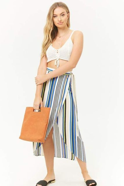 With white crop top, brown bag and black flat sandals