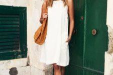 With white dress and brown suede bag