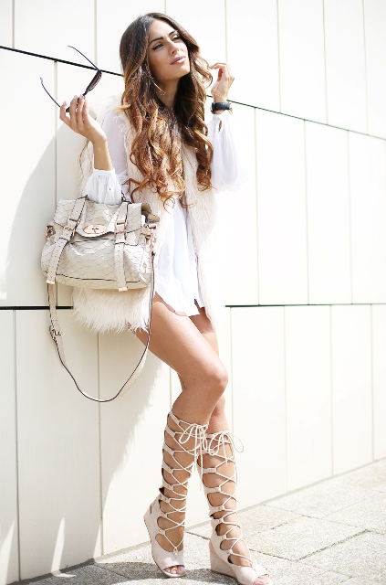 With white mini dress, fur vest and white bag