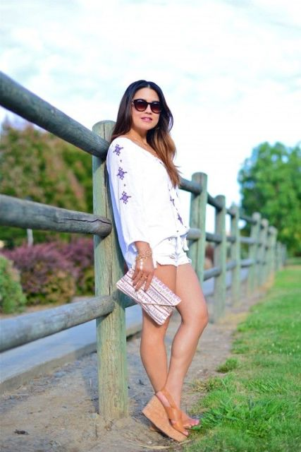 With white shorts, loose shirt and printed clutch