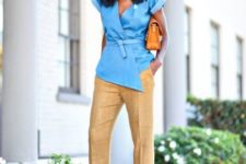 With wide leg trousers, orange clutch and high heels