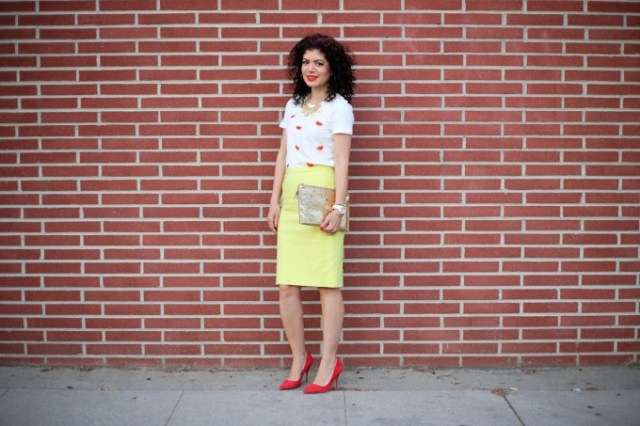 With yellow knee-length skirt, clutch and red pumps