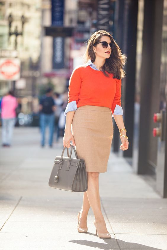 a chic and bold look with nude shoes, a neutral knee skirt, a blue shirt plus an orange top, a grey bag