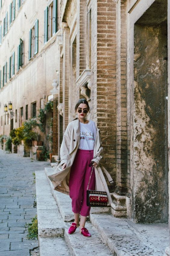 a logo t-shirt, fuchsia wideleg pants and flats, a tan trench and a printed bag