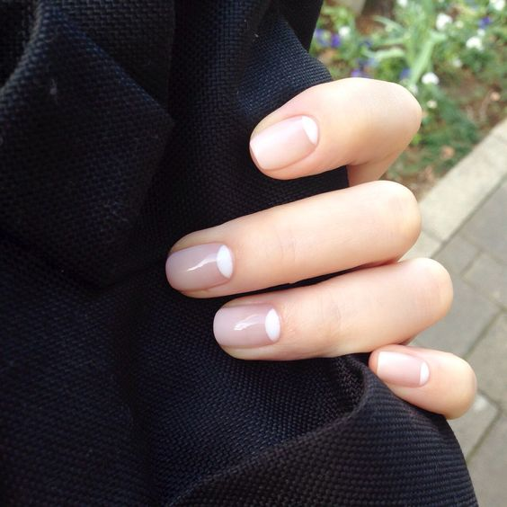 a reverse French manicure with nude and white is a chic idea