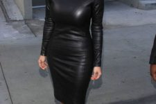03 Kim Kardashian wearing a black leather sheath dress with long sleeves and black lace shoes