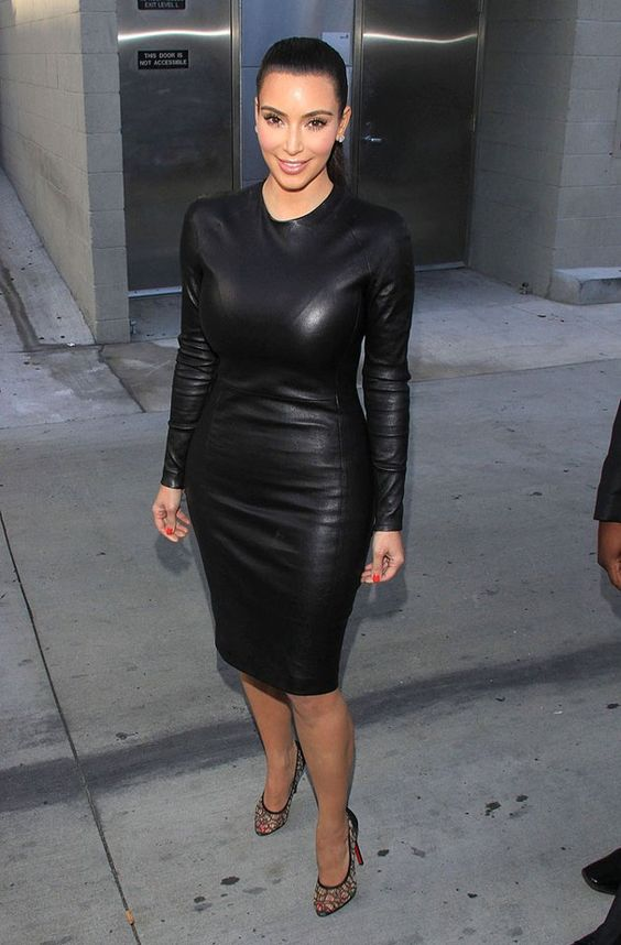 Kim Kardashian wearing a black leather sheath dress with long sleeves and black lace shoes