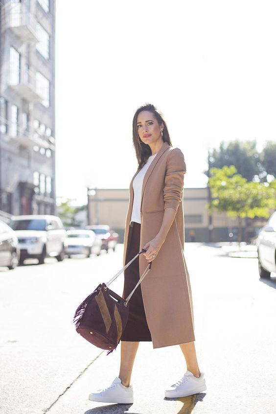 a casual work look with a white top, a burgundy midi skirt, a camel coat and white sneakers