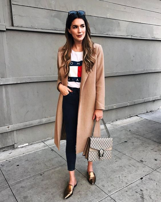 a logo t-shirt, navy cropped jeans, a tan coat and metallic shoes