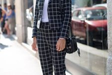 03 a plaid black and white suit, a white tee, white sneakers and a black bag