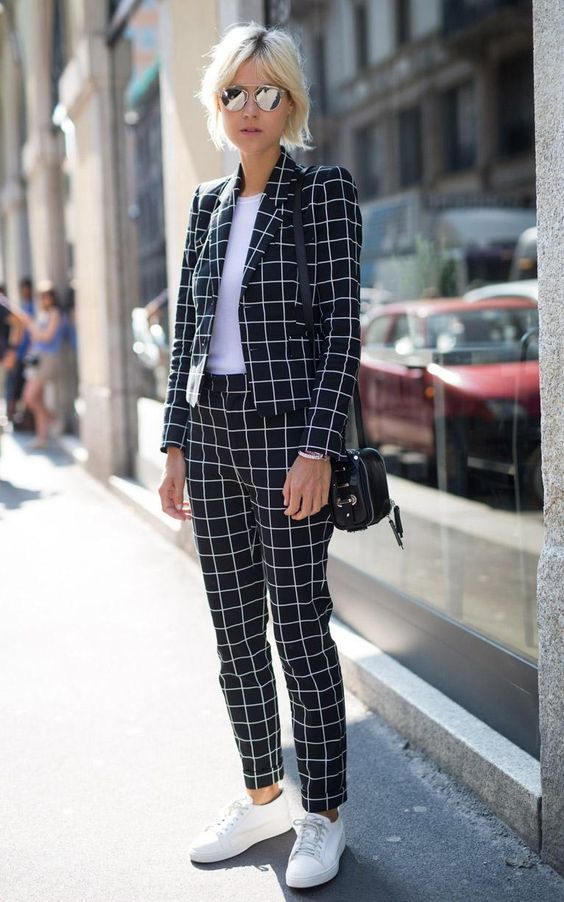 a plaid black and white suit, a white tee, white sneakers and a black bag