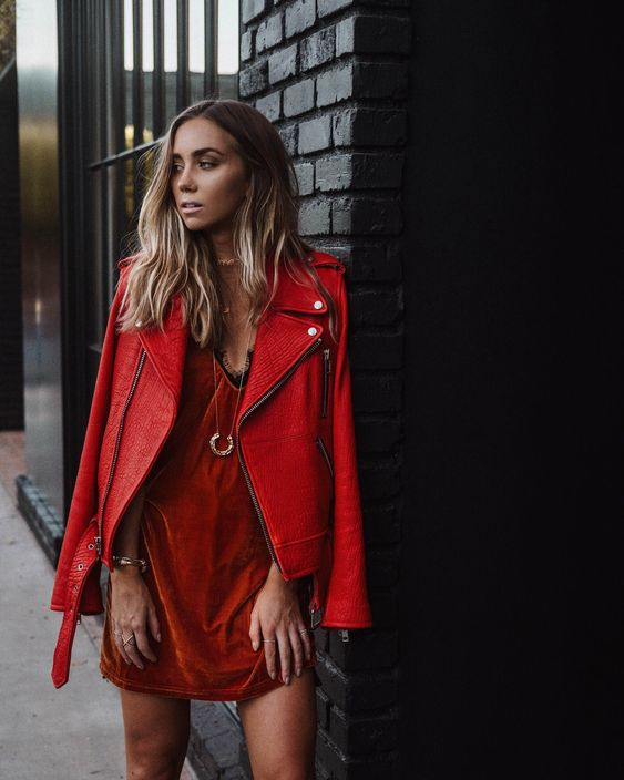 a rust velvet dress with a lace neckline, a red leather jacket and boots