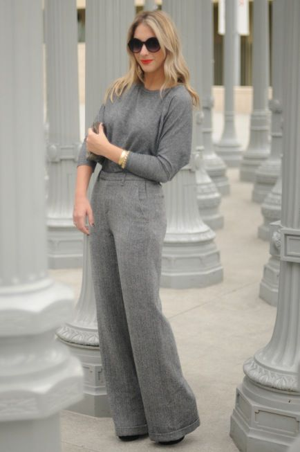 grey wideleg pants, a grey top, black booties and a statement bracelet