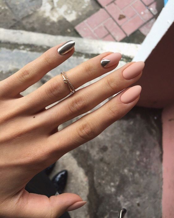 matte nude nails with a silver statement nail and a geometric detail for a trendy look