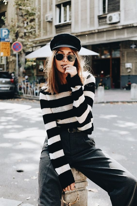 tweed pants, a striped sweater and a black cabbie hat is a trendy look for fall
